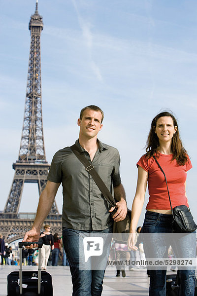 Tourist couple walking with their luggage near Eiffel Tower  Paris  France