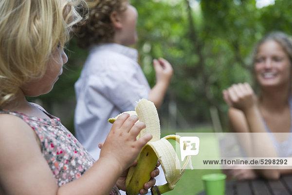 Kleines Mädchen im Freien mit ihrer Familie  das Banane isst.