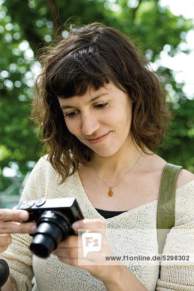 Frau betrachtet Digitalkamera
