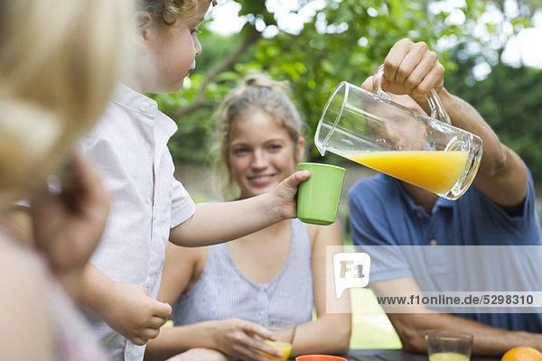 Family together outdoors  father pouring glass of juice for son