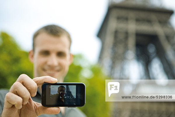 Man photographing himself in front of Eiffel Tower  Paris  France