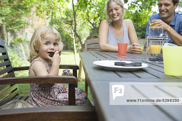 Little girl eating snack with her parents outdoors