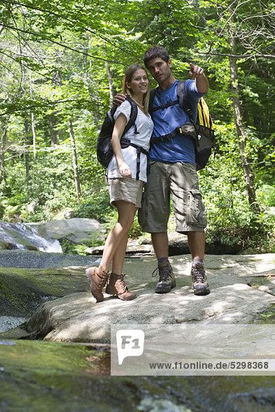Paar steht am Bach im Wald