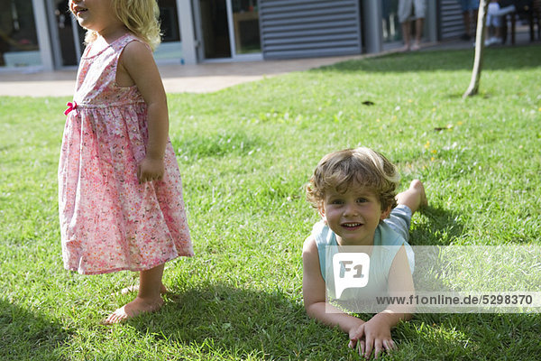 Boy playing on lawn with his sister