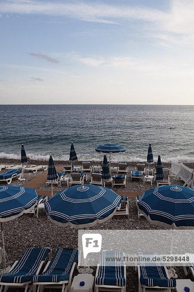 Sonnenschirme und leere Liegestühle am Strand