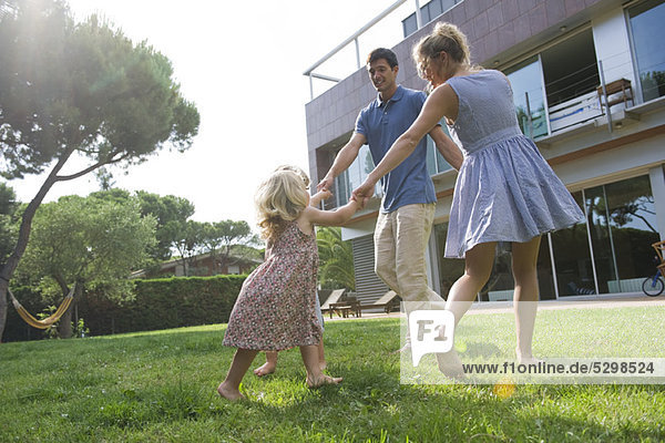 Family playing ring-around-the-rosy outdoors