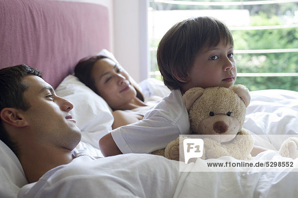 Boy sitting in bed with his parents and his teddy bear