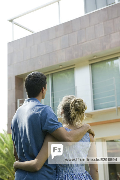 Couple standing together  looking at home  rear view