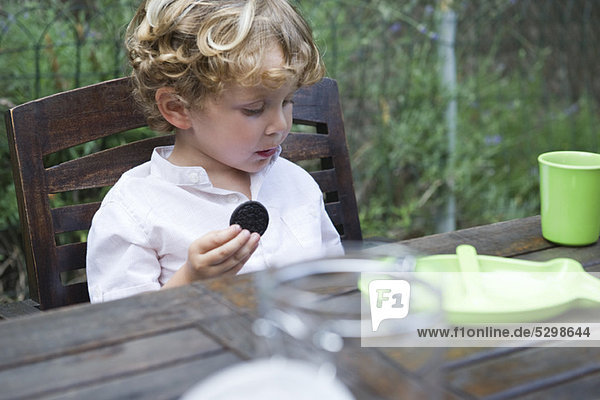 Boy eating cookie outdoors