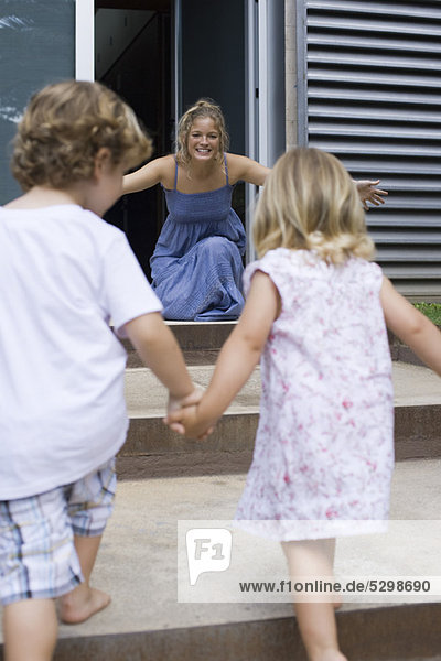 Young siblings holding hands  running toward mother