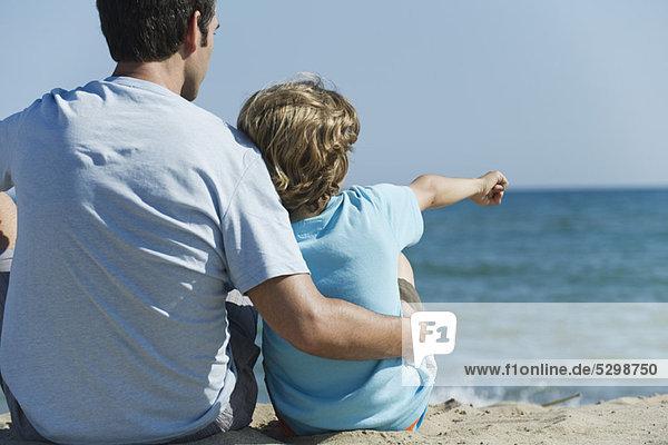 Vater und Sohn sitzen zusammen am Strand  Junge zeigt auf das Meer.