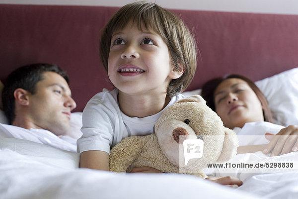 Boy sitting in parents' bed  hugging teddy bear