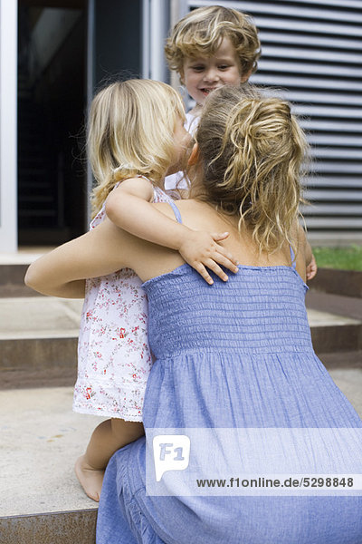 Mother hugging young daughter outdoors