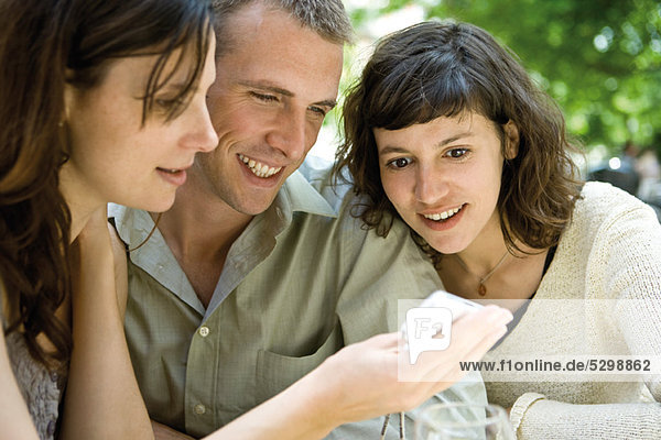 Friends looking at cell phone outdoors