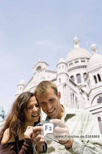 Sightseeing-Paar mit Blick auf Digitalkamera  Sacre Coeur  Montmartre  Paris  Frankreich