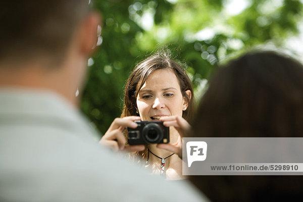 Frau fotografiert Paar mit Digitalkamera  über die Schulter gesehen