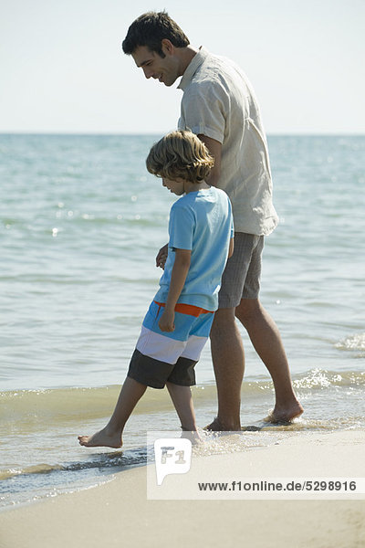 Father and son walking in surf at the beach
