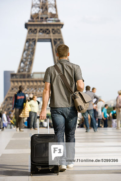 Male tourist walking with luggage  Eiffel Tower  Paris  France
