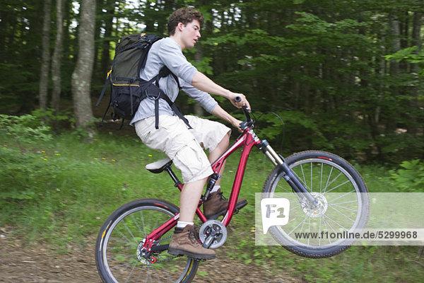 Mann  der auf dem Mountainbike Wheelie fährt.