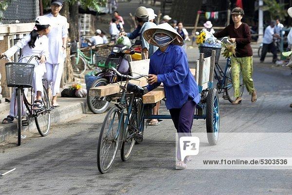 kegelförmig Kegel Frau schieben über Hut Stadt Geschichte Holz Mittelpunkt Camcorder Fahrrad Rad Vietnam
