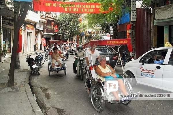 Visitors on cyclo rickshaw group tour of Old Quarter Ma May Street Hanoi Vietnam