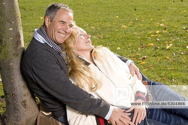 Happy mature man embracing woman in park