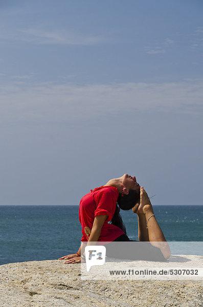 Frau in Yoga-Position Bhujangasana  am Meer in Kanyakumari  Tamil Nadu  Indien  Asien