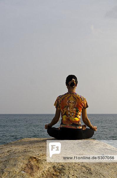 Frau in Yoga-Position Padmasana  am Meer in Kanyakumari  Tamil Nadu  Indien  Asien