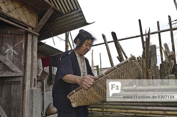 Frau des Apatani-Stammes bei der Reinigung der Ernte auf traditionelle Art  Dorf Hong in den Hügel der Region Ziro  Arunachal Pradesh  Indien  Asien