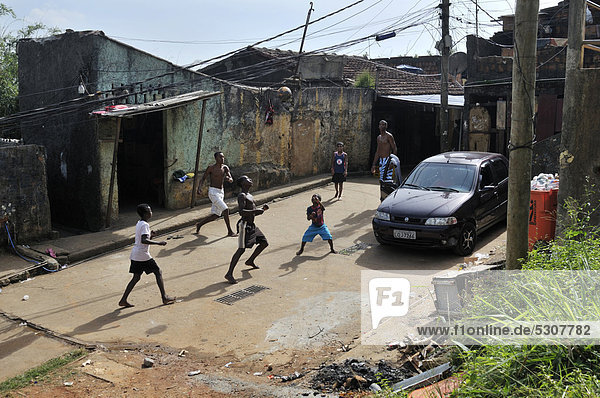 Youths playing football in the street  slum district of Favela Morro da Formiga  Tijuca district  Rio de Janeiro  Brazil  South America