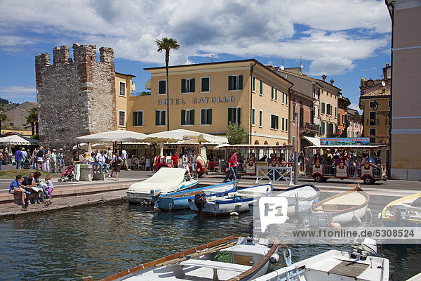 People  fishing boats in the harbour  ruins of the tower of a Scaliger castle  Hotel Catullo  Bardolino  Lake Garda  Verona Province  Veneto  Italy  Europe