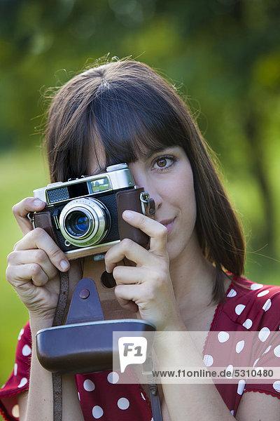 Junge Frau  25 Jahre  mit alter Kamera
