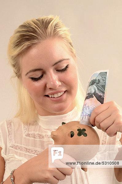 Lächelnde  junge  blonde Frau steckt einen schwedischen Geldschein in ein Sparschwein