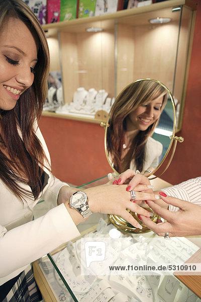 Junge Frau probiert Ring im Juweliergeschäft an