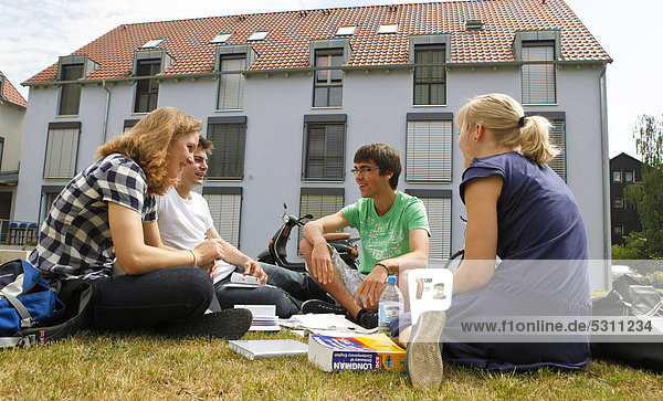 Group of students sitting on lawn in front of dormitory