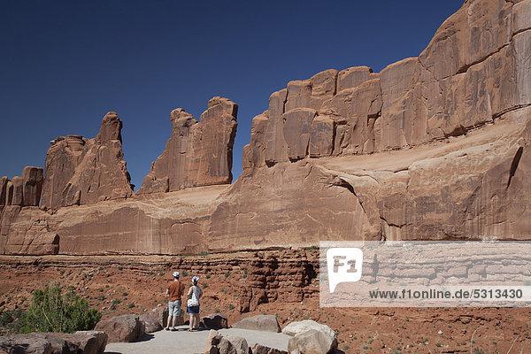 Pärchen betrachtet eine der Felswände der Park Avenue im Arches-Nationalpark  Moab  Utah  USA