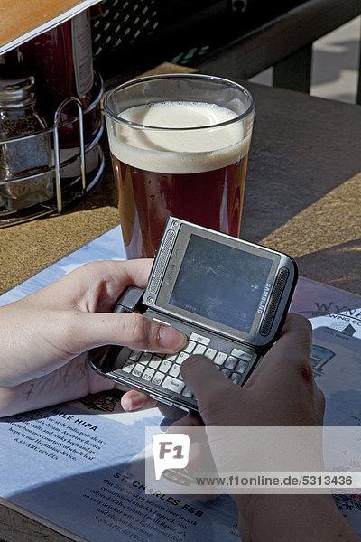 Frau schickt eine SMS  am Tisch eines Straßencafes  Denver  Colorado  USA