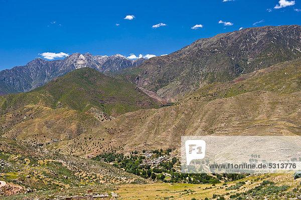 Berglandschaft im Hohen Atlas  im Tal liegt eine kleine Siedlung der Berber umgeben von Bäumen  Passstraße Tizi-n-Test  Südmarokko  Marokko  Afrika