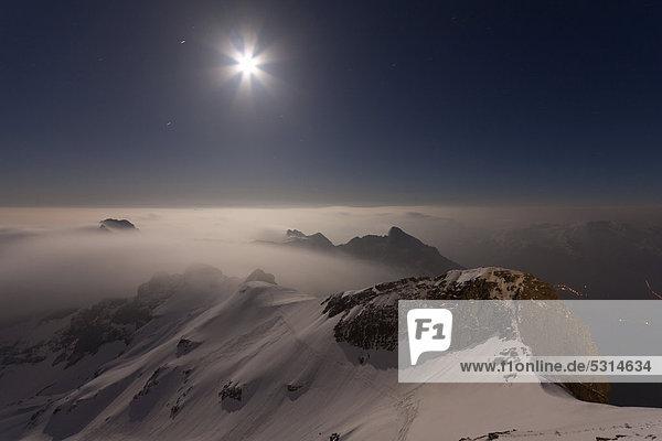 Nachtaufnahme  bei Vollmondlicht ragt der Alpstein aus dem Nebelmeer heraus  Säntis  Alpstein  Appenzell Ausserrhoden  Appenzell Innerrhoden  Schweiz  Europa  ÖffentlicherGrund