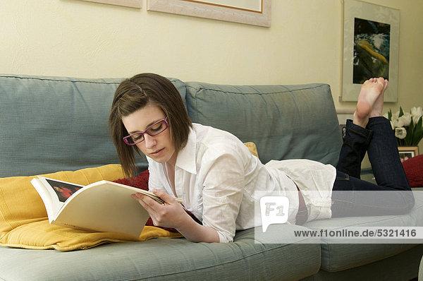 Mädchen liegt auf einem Sofa und liest eine Zeitschrift