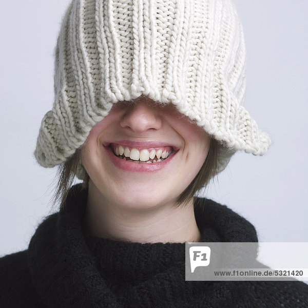 Girl wearing a woolen hat  covering eyes  smiling