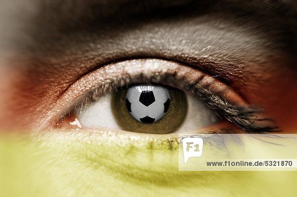 Ein Fußball spiegelt sich in einem Frauenauge  Frauen-Fußball