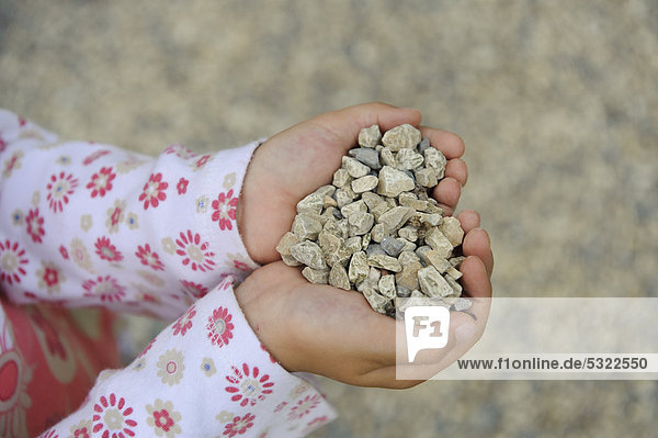 Hands of a five-year-old girl filled with pebbles  making a heart