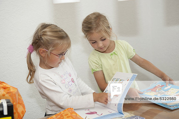 Two girls  4 and 5 years  reading books