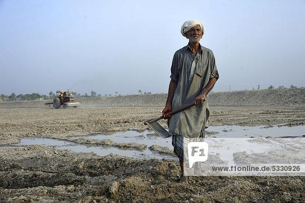 Alter Mann beim Ausheben eines Fischteiches  Dorf Basti Lehar Walla  Punjab  Pakistan  Asien