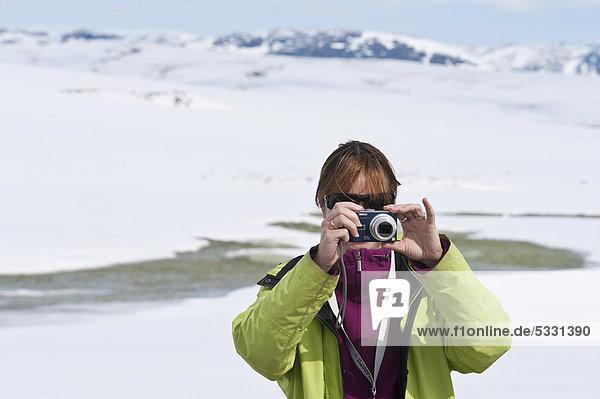 Junge Frau  fotografiert mit Digitalkamera am Hardanger Vidda  Hardangervidda  Norwegen  Skandinavien  Nordeuropa