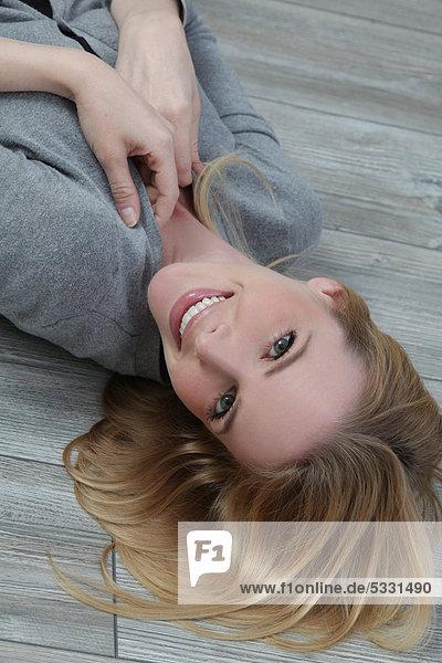 Junge blonde Frau lächelt in die Kamera