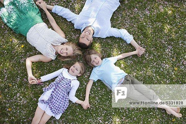 Familie liegt zusammen im Gras