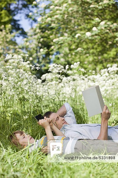 Vater und Sohn entspannen im Gras
