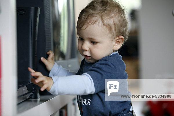 Kleiner Junge  1 Jahr  erkundet DVD-Spieler